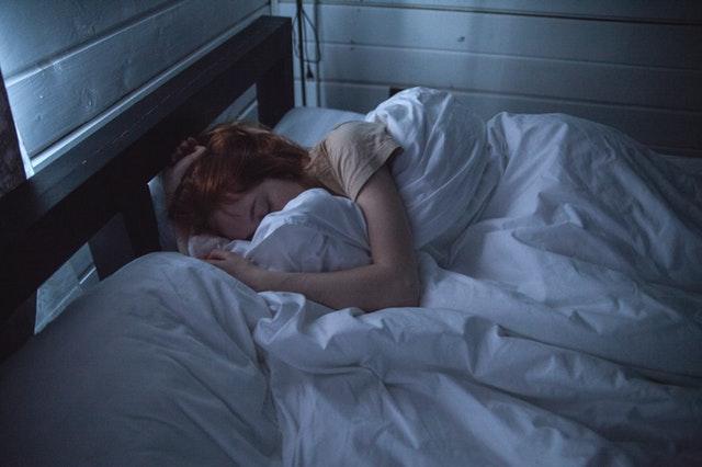 Žena spí zakrytá bielym paplónom v posteli