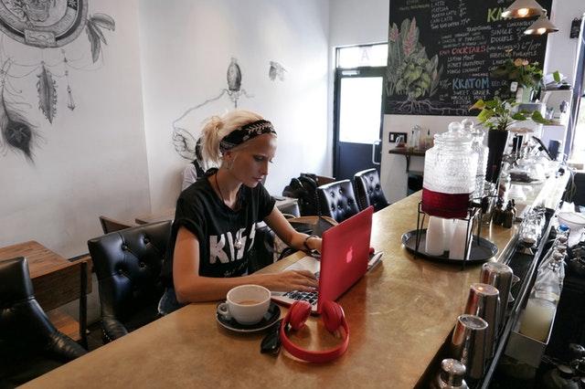 Žena v čiernom tričku KISS sedí v kaviarni a píše na notebooku.jpg