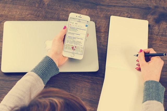 Žena sa pozerá do telefónu a robí si poznámky na papier.jpg