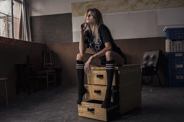 Žena v tričku a podkolienkach sedí na drevenej poličke.jpg