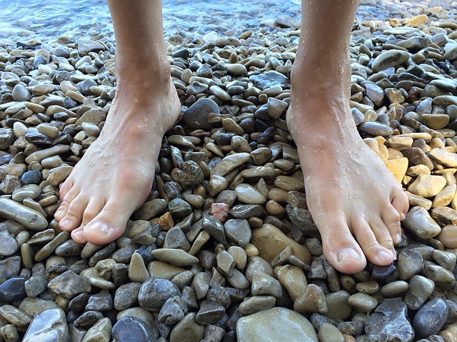 Muž s bosými nohami stojí na kamenistej pláži pri vode.jpg