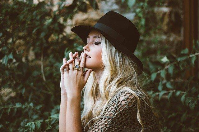Žena v klobúku s množstvom prsteňov na rukách