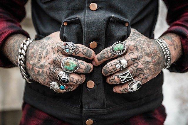 Muž s potetovanými rukami, prsteňmi a náramkami