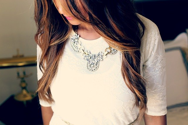 Žena v bielych šatách s veľkým náhrdelníkom